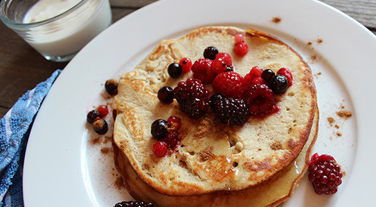 a plate of pancakes topped with berries