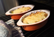 Sizzling cauliflower cheese bake coming out from under the grill